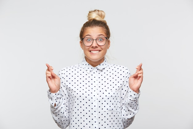 Portrait of confident attractive young woman with bun wears polka dot shirt and spectacles