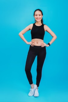 Portrait of confident beautiful asian fitness woman standing after exercise isolated on blue color.