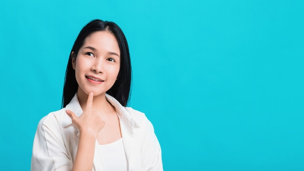Portrait of confident beautiful asian woman thinking and smiling isolated on blue color background.