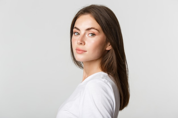 Portrait of confident beautiful brunette woman turning face at camera with dreamy look, white.