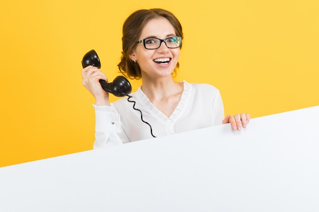 Portrait of confident beautiful excited smiling happy young business woman with telephone showing blank billboard on yellow background