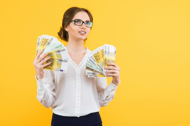 Portrait of confident beautiful happy young business woman with money in her hands standing