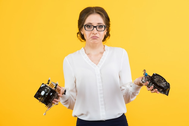 Portrait of confident beautiful puzzled confused young business woman with equipment computer parts