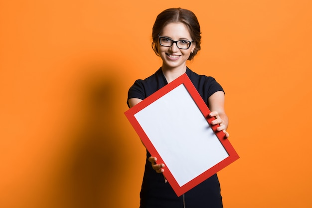 Portrait of confident beautiful young business woman holding frame in her hands standing on orange tshirt offering