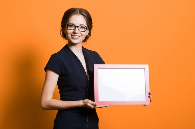 Portrait of confident beautiful young business woman holding frame in her hands standing