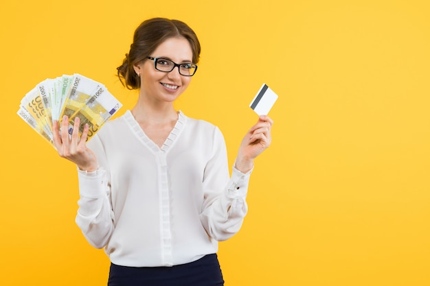 Portrait of confident beautiful young business woman with money and credit card in her hands standing on yellow