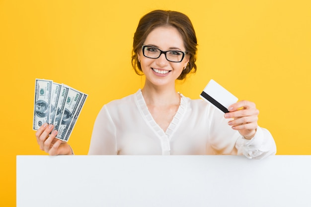 Portrait of confident beautiful young business woman with money and credit card in her hands with blank billboard on yellow
