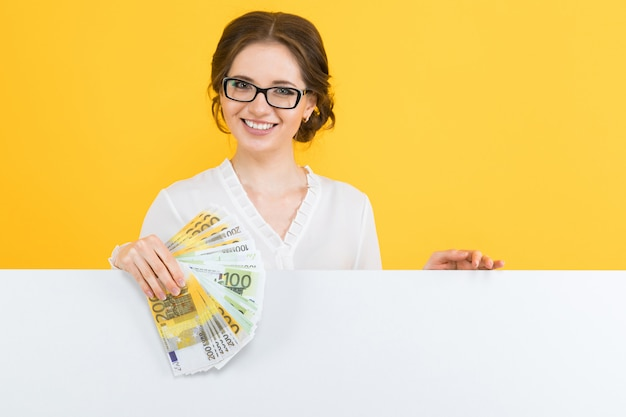 Portrait of confident beautiful young business woman with money in her hands and blank billboard on yellow