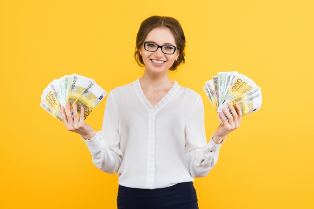 Portrait of confident beautiful young business woman with money in her hands standing on yellow