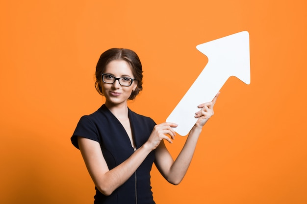 Portrait of confident beautiful young business woman with paper pointer in her hands standing on orange