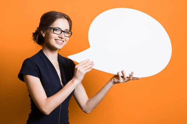 Portrait of confident beautiful young business woman with speech bubble in her hands standing on orange wall