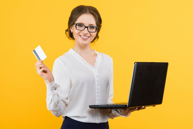 Portrait of confident beautiful young smiling business woman with laptop offering credit card on yellow