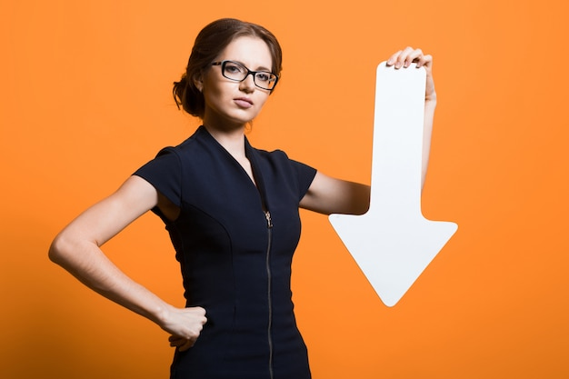 Portrait of confident beautiful young successful business woman with paper pointer in her hands standing on orange background