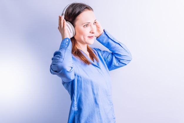 흰색 배경에 음악 헤드폰을 들고 있는 자신감 있는 아름다운 젊은 여성의 초상화. 음악을 듣거나 즐기는 개념