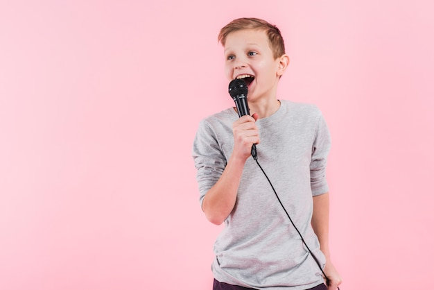 Portrait of a confident boy singing song on microphone against pink background