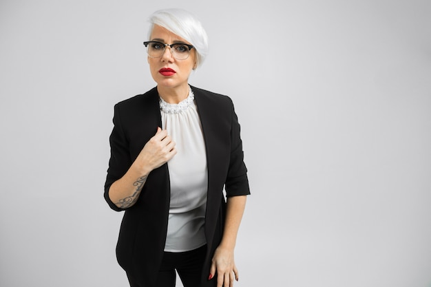 Portrait of a confident business lady in a strict suit isolated on a light
