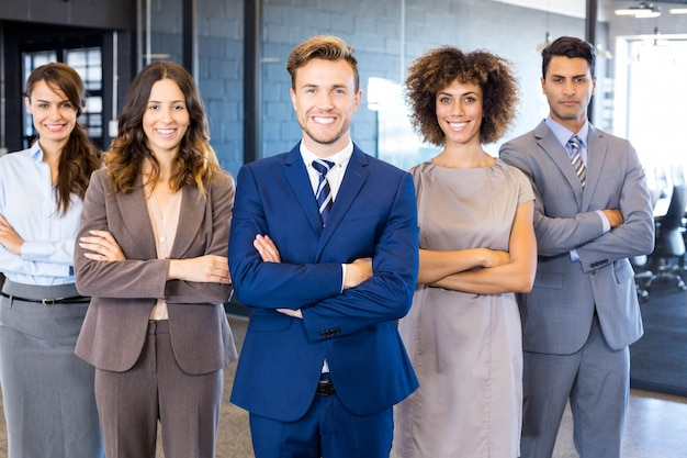 Portrait of confident business  team standing in office with their hands crossed