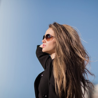 Portrait of confident business woman on the background of blue sky in the city