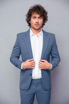 Portrait of a confident businessman standing over gray wall and looking at front