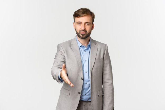Portrait of confident businessman with beard, extending hand for handshake