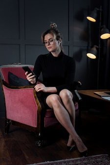 Portrait of confident businesswoman checking her phone