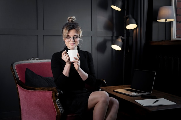 Portrait of confident businesswoman having coffee