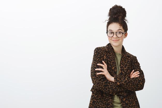 Ritratto di imprenditore femminile creativo spensierato fiducioso in occhiali alla moda e cappotto leopardato, tenendo le mani incrociate e sorridendo sicuro di sé