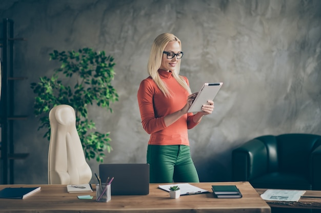 Portrait of confident cool leader woman stand in her office loft work on tablet reading start-up news wear orange turtleneck green pants trousers