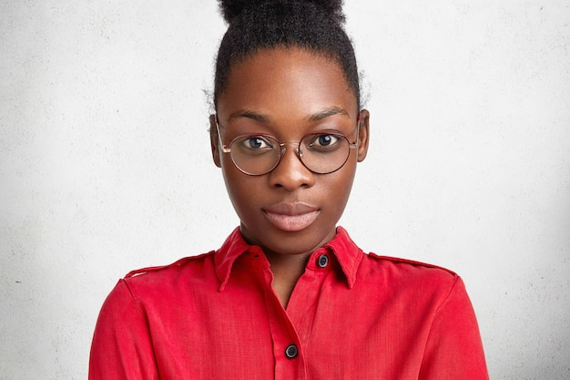 Portrait of confident dark skinned woman enterpreneur with serious look, wears round glasses and red blouse, going to meet with partners from abroad, prepares for presenting company, isolated on white