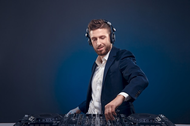 Portrait of confident dj with stylish hair style and mixing table