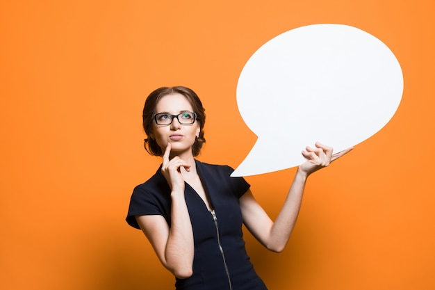 Portrait of confident excited beautiful young business woman with speech bubble in her hands standing on orange