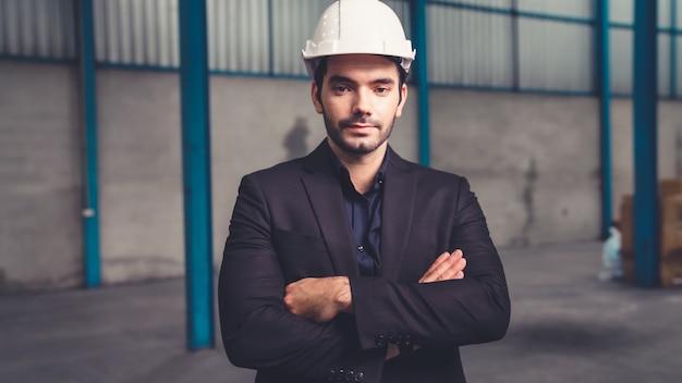 Портрет уверенно управляющего фабрикой в костюме и защитной каске на фабрике. промышленно-инженерная концепция.
