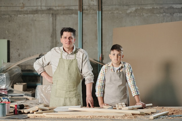 Portrait of confident father and son in aprons standing at desk with wooden planks in carpentry workshop, family business