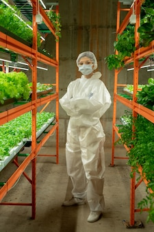 Portrait of confident female agronomist in protective suit, mask and cap standing with crossed arms between vertical farm shelves