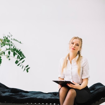 Portrait of confident female psychologist sitting on couch holding clipboard