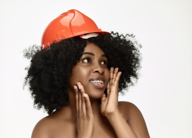 Portrait of confident female worker in orange helmet