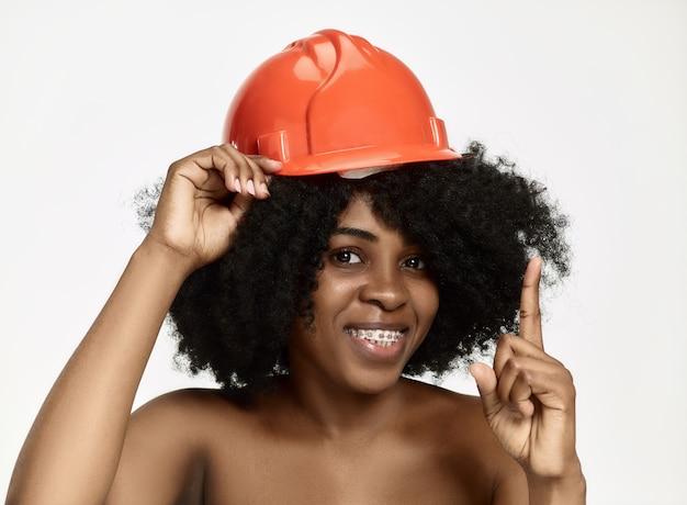 Portrait of confident female worker in orange helmet