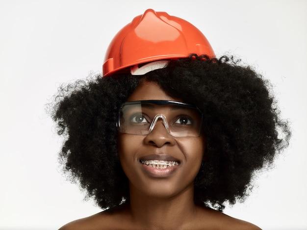 Ritratto della lavoratrice fiduciosa in casco arancione