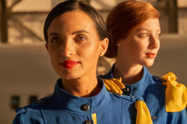 Portrait of a confident flight hostess in blue uniform standing outdoors with her younger colleague and smiling