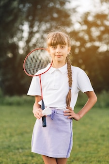 Portrait of a confident girl standing with badminton and shuttlecock