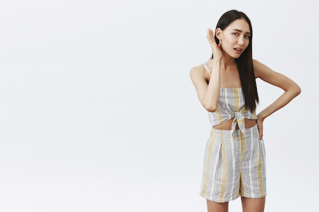 Portrait of confident good-looking asian stylish female holding palm near ear and hand on waist, asking repeat question cause unheard