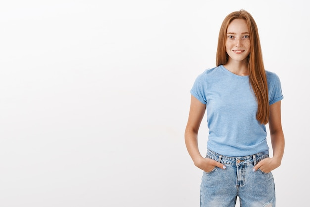 Portrait of confident good-looking ginger girl with cute freckles in blue t-shirt and jeans holding hands in pockets and smiling with self-assured expression