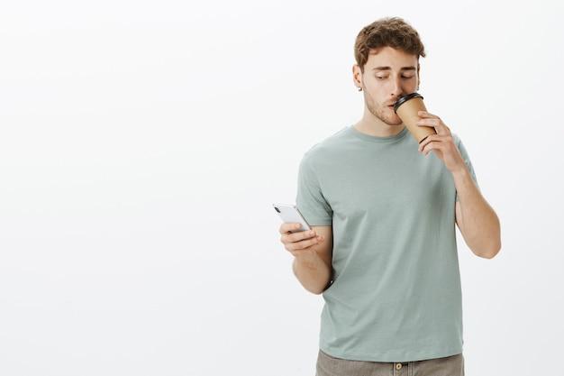 Ritratto di fiducioso imprenditore maschio di bell'aspetto in orecchini, tenendo lo smartphone e bevendo una tazza di caffè mentre risponde al messaggio e guarda lo schermo