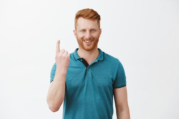 Portrait of confident good-looking mature european masculine redhead male with bristle in green polo shirt, showing number one with index finger and smiling pleased