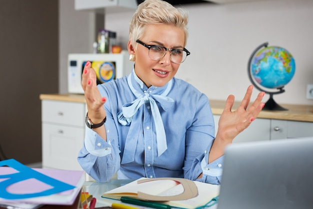 Portrait of confident good looking teacher sitting at table