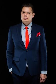 Portrait of confident handsome businessman on black