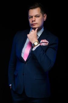 Portrait of confident handsome businessman holding hand near beard on black  thinking waiting