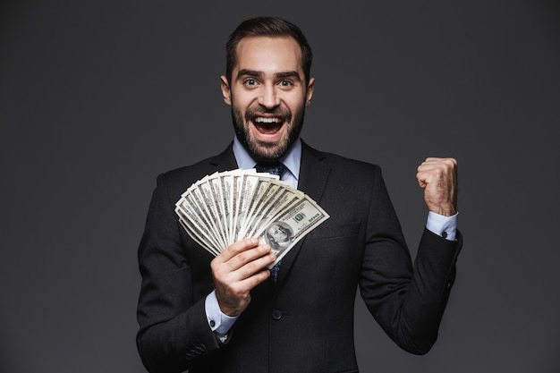 Portrait of a confident handsome businessman wearing suit isolated, showing money banknotes