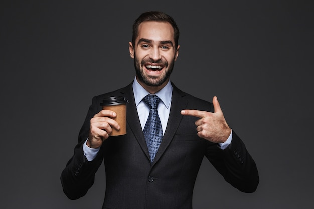 Portrait of a confident handsome businessman wearing a suit standing isolated, holding takeaway coffee cup