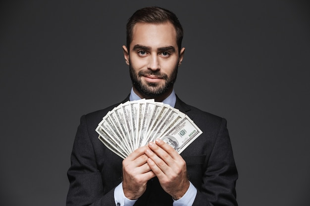 Portrait of a confident handsome businessman wearing a suit standing isolated, showing money banknotes
